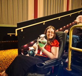 """Veronica holding Hestia in the movie theater. You an clearly see Hestia's new bandana that is green and yellow and says """"Service Dog Hestia"""""""