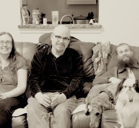 A black and white photo of Veronica, CJ, Brad, Ollie, and Hestia. Brad has a big bushy beard. Ollie is a shaved standard poodle. Hestia is a small black and white dog with a smushed face.