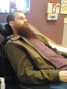 Brad in a purple shirt and green sweater, reclining in his wheelchair at the doctor's office