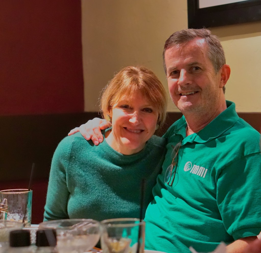 Dan and Betsey, both wearing green for St. Patrick's Day.  Dan has his arm around Betsey's shoulder.
