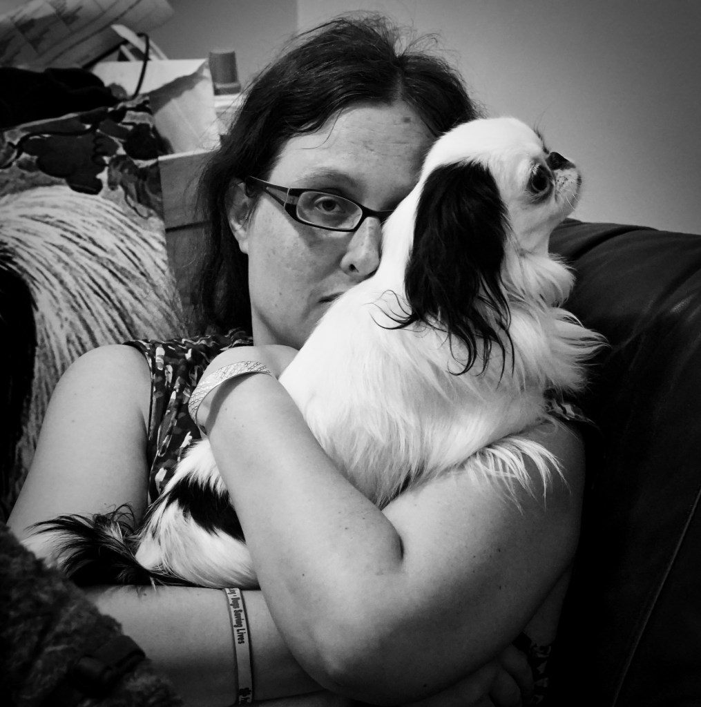 Black and white picture of a concerned, unhappy, and anxious Veronica holding Hestia to her chest and in front of half of her face.
