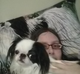 Hestia, a small black and white dog, looks at the camera from atop Veronica's chest. Veronica, a 30 something with purple and orange classes is mostly obscured by a Hestia body and head!