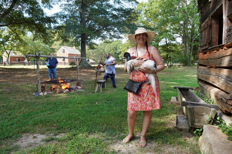 Veronica holding Hestia in front of a fire that is being built in order to cook some pork.