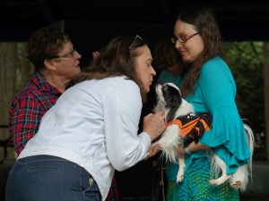 Veronica in turquoise holding Hestia (wearing a black and orange dress). Judy, a woman in a white jacket, is bending over to kiss Hestia while I talk with another person close by.