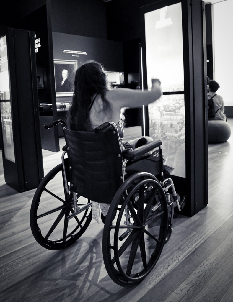 Black and White picture of Veronica in a wheelchair from behind, interacting with a display at the museum.