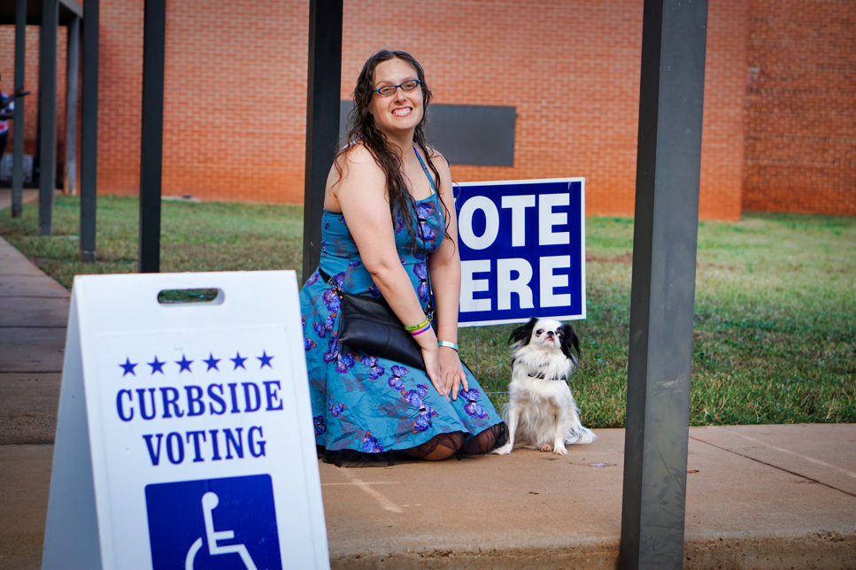 """Veronica kneeling and Hestia on the ground looking at the camera cutely.  They are in front of the """"vote here"""" sign, and also behind the curbside voting sign."""