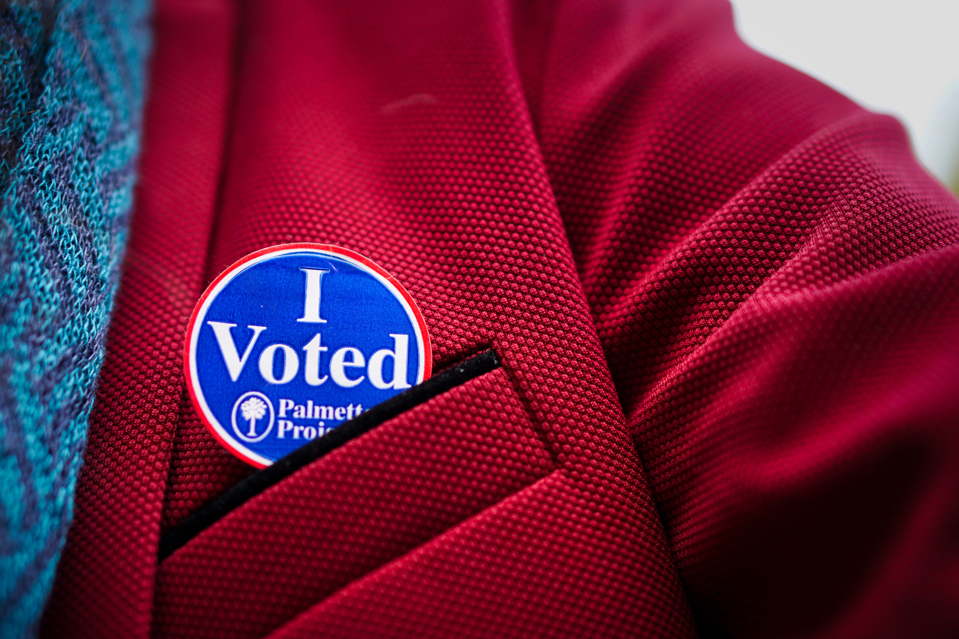 """Closeup of Brad's """"I voted"""" blue sticker on Brad's red blazer.  You can see the texture of the fabric, and it looks very cool."""