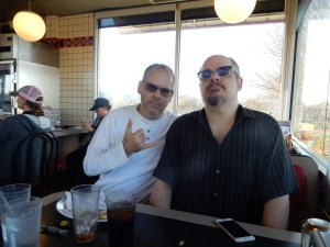 Dan and CJ, looking cool at Waffle house.  Dan has a white shirt on, and CJ has a black one.  Both of their glasses are dark like sunglasses.  Dan is holding his hand up in a sign language Y, and CJ is lifting his head like he is just too cool.