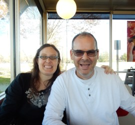 Dan and me at Waffle House. I am wearing a black shirt, and have my arm around Dan. We are both smiling widely!