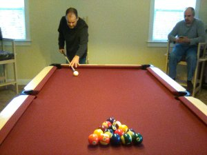 Dan getting ready to break. Red pool table, Man in black with short black hair about ready to hit the white ball.