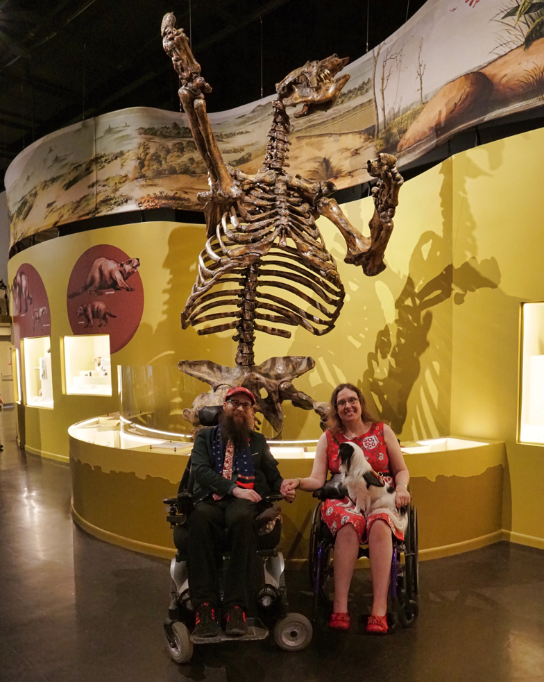 Veronica and Brad, both in wheelchairs, hold hands in front of the skeleton of a pre-historic giant sloth.