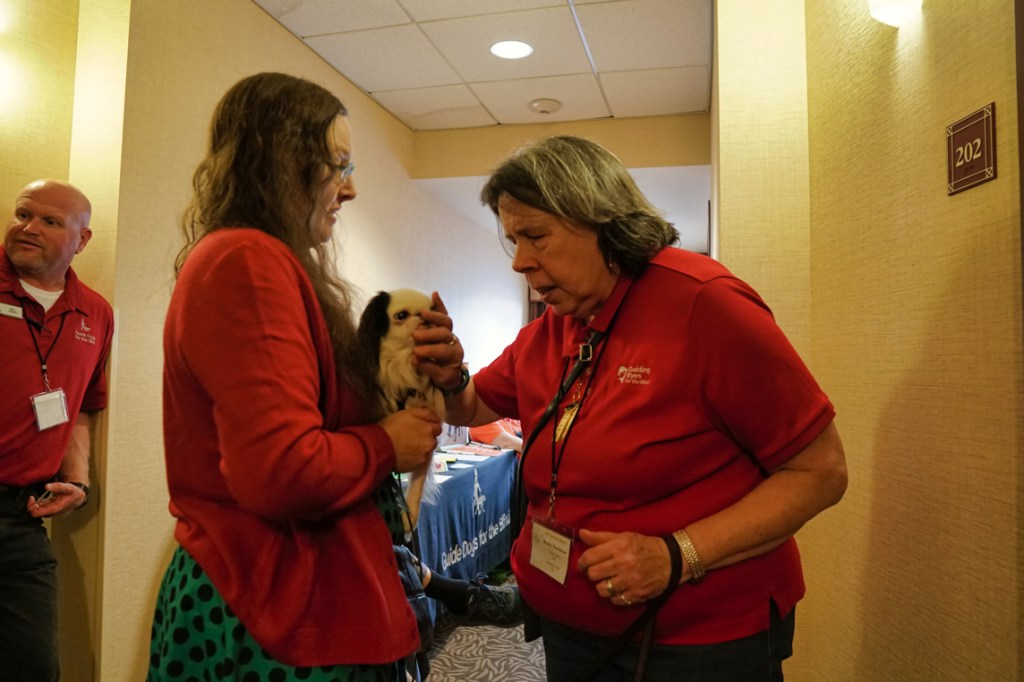 A common sight at the Top Dog conference-- a woman feels Hestia's face (with permission) to see what a crazy-looking dog she is!  Hestia looks ahead stoically.  Veronica is wearing a turquoise and black polka-dot dress with a red sweater.