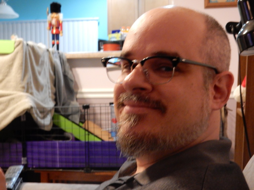 """A closeup of a man with a beard and glasses, with a guinea pig cage in the background. His glasses and style are very """"cool"""""""