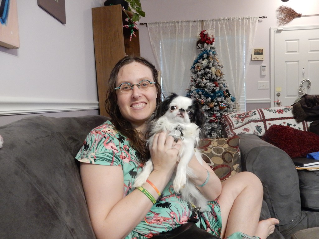 A late 30s woman in a pink flamingo dress with long curly brown hair and round turquoise glasses holds a small black and white dog.  There is a Christmas tree in the background.