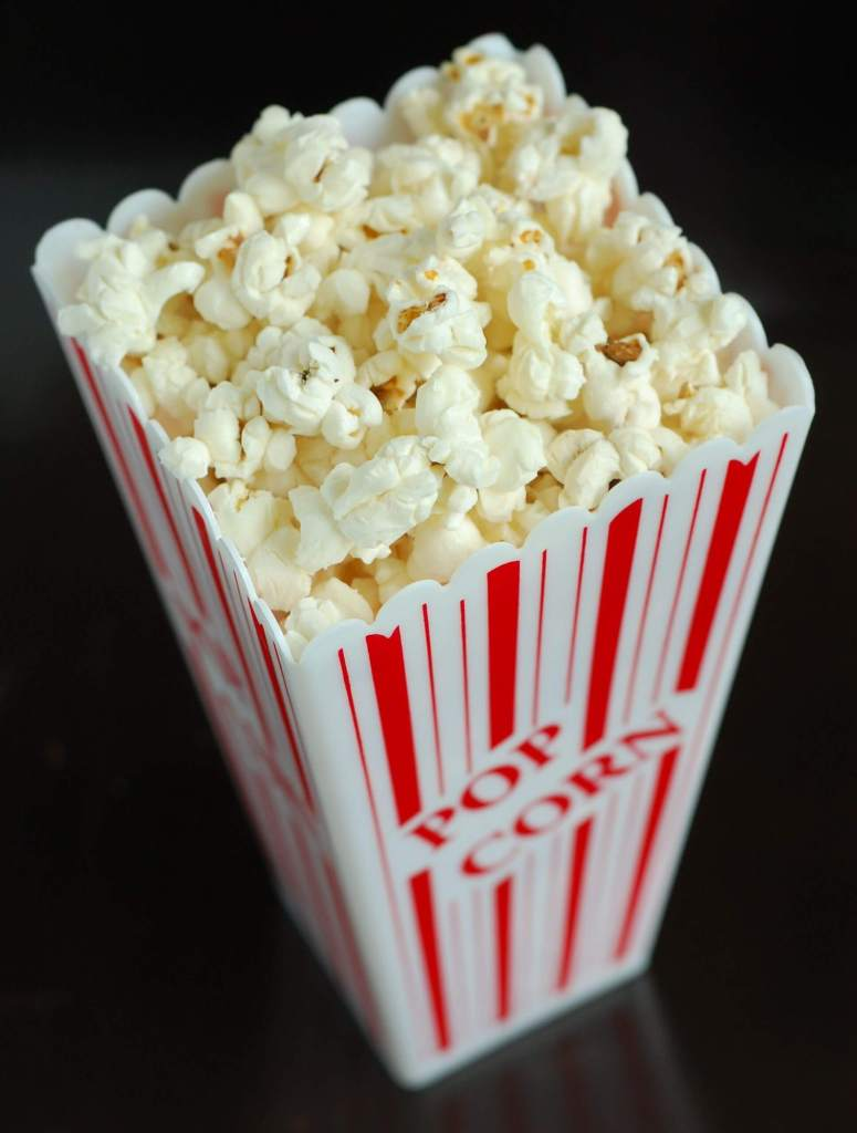 A red and white striped popcorn container filled with yellow popcorn.