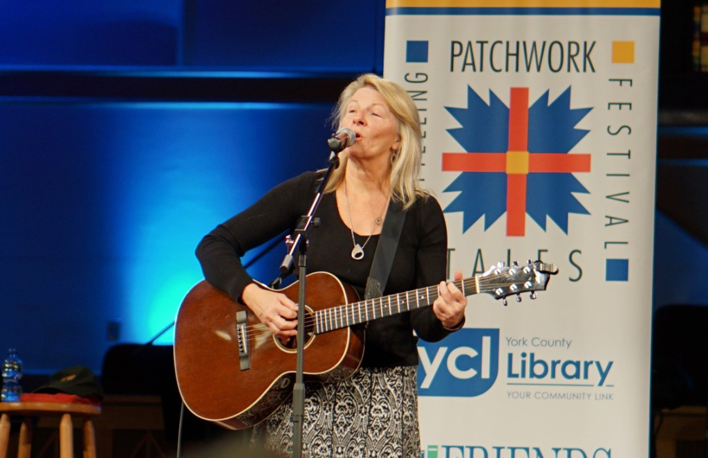 The woman is singing in front of a banner for the patchwork storytelling festival