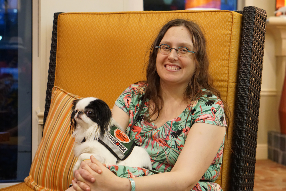Veronica, a woman with long curly brown hair, wears a Flamingo dress as Hestia, a Japanese Chin, sits on her lap