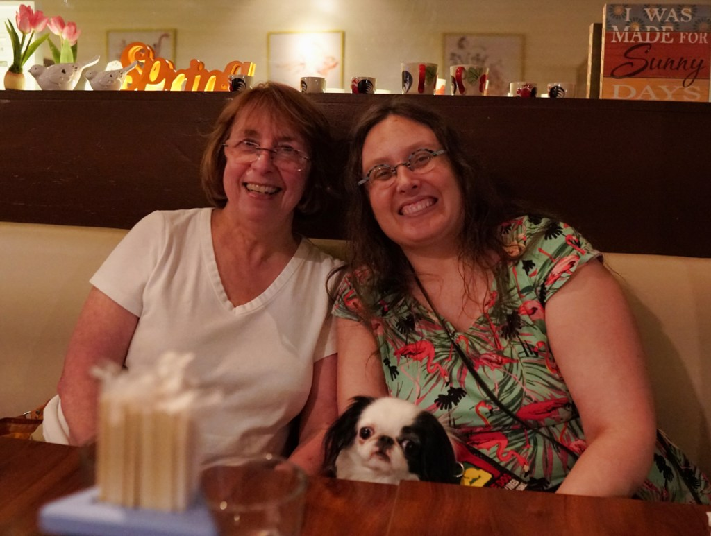 Gerry (a woman in a white shirt with glasses) and Veronica (a woman in a pink flamingo dress) at a Thai restaurant with Hestia's small black and white head peeking up over the table.  Both women are smiling!