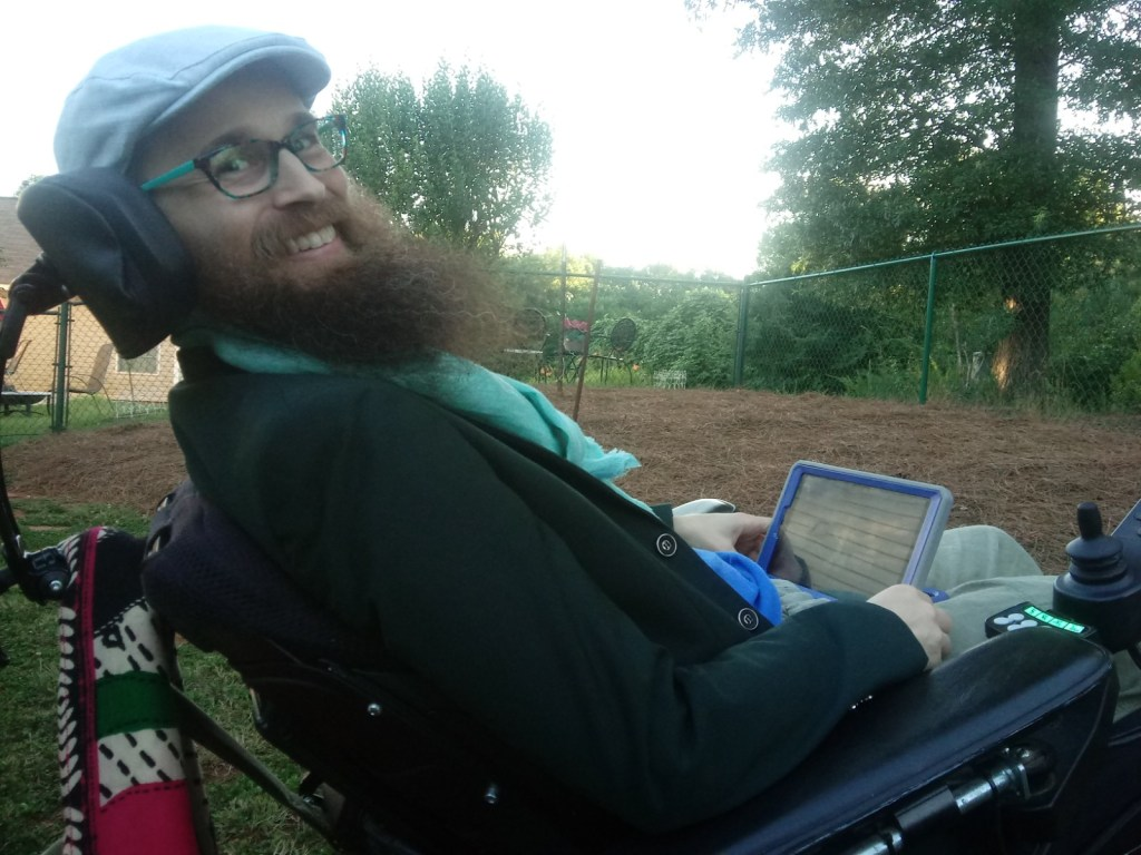 Brad in his wheelchair looking at the camera and smiling.  In the background are a green wire fence and lots of trees.