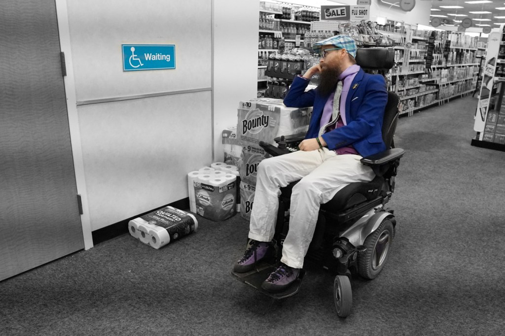 """This picture is mostly black and white, with just the wheelchair waiting sign and Brad in color.  In this zoomed out shot, you can see that there is no way for a wheelchair to fit in this space!  Brad rests his arm on the stack of paper towels and looks contemplatively at the sign.  Brad's caption for this picture is """"choose your own caption""""-- so put yours in the comments!"""