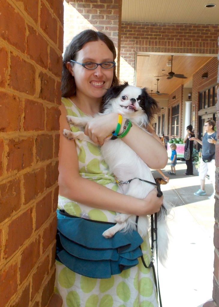 Hestia looks happy to be cuddled as Veronica holds her during a dog training class