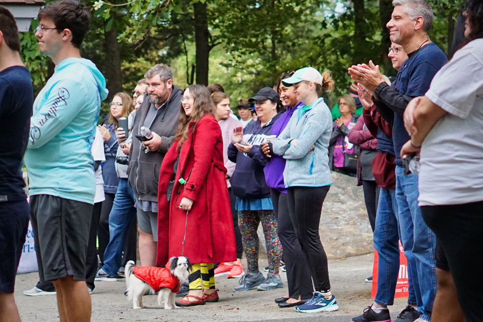The crowd, including Veronica and Hestia, laughs and claps at something being said in the speeches before the walk.