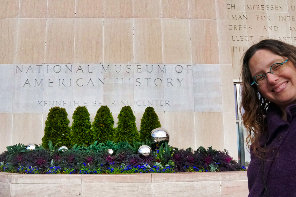 A sign for the National Museum of American History with Veronica smiling in the corner of the picture.