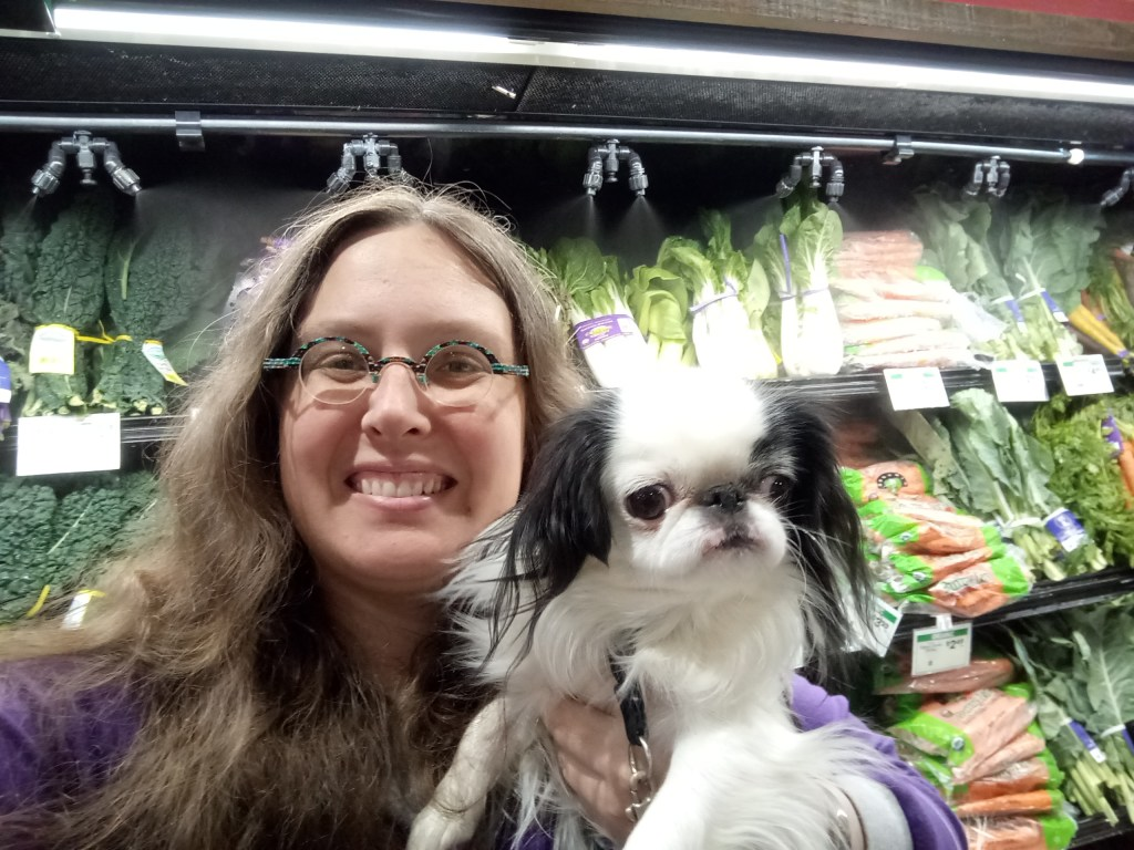 Veronica, a woman with long brown wavy hair and round turquoise glasses holds Hestia close and takes a selfie.  In the background is the greens section of the grocery store.