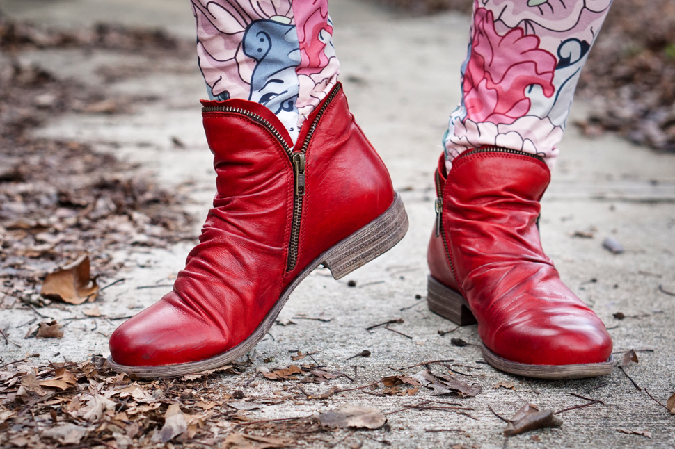 Red leather boots with a ruched pattern.  Veronica has one foot raised onto her toe—posing smartly, not to bring an end to any unfortunate life with an exoskeleton. The rich red of the boots and reds and pinks of the leggings offer a strong contrast to the grays and composting browns of the driveway and its leafy detritus.