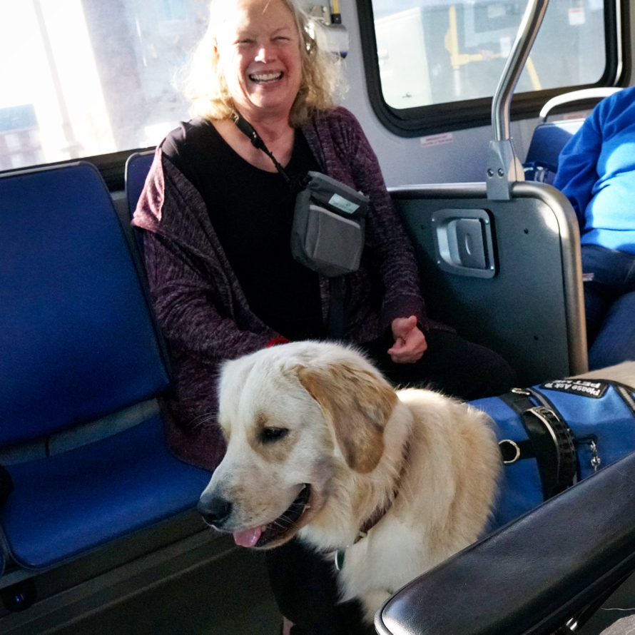 Barbara smiles as Tripper stands and looks forward on the bus.