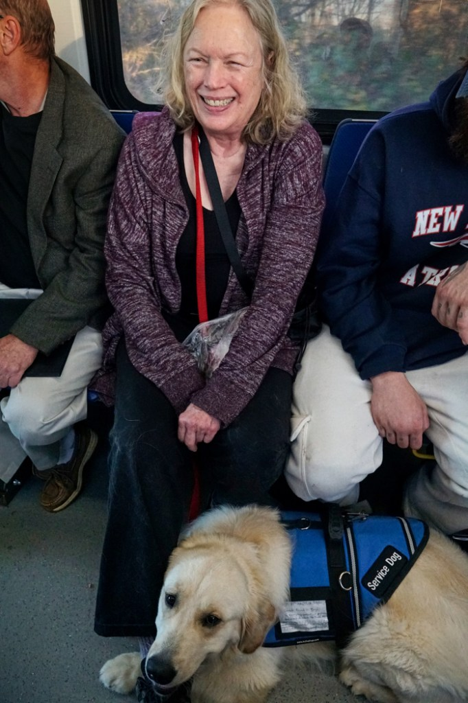 Barbara smiles while Tripper lies at her feet on the bus.