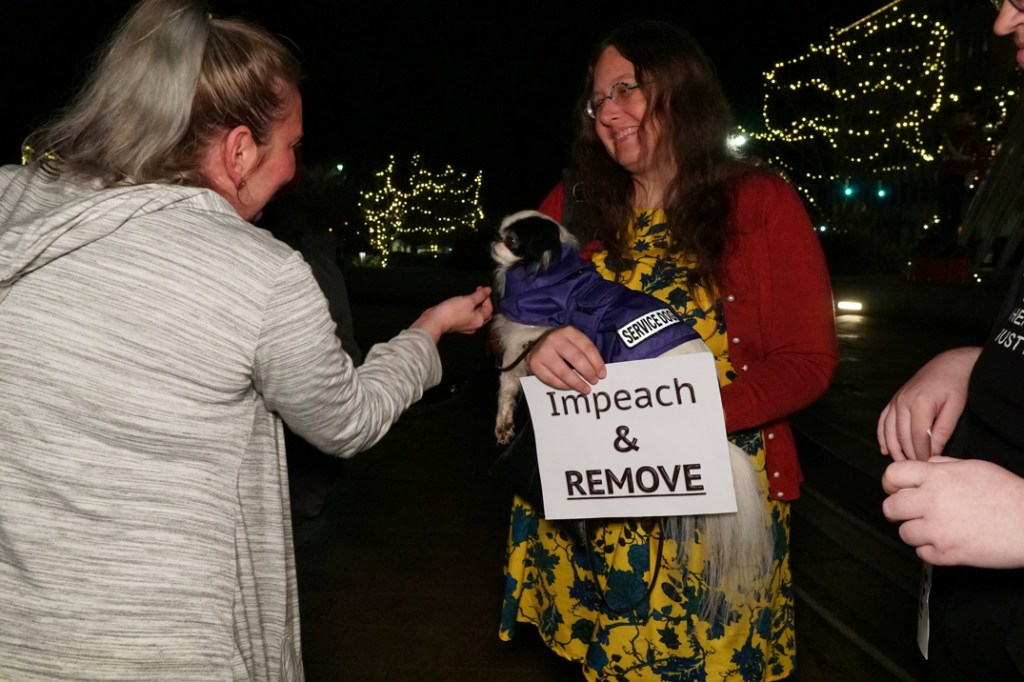 Veronica smiles while holding Hestia and her sign at a person who is petting Hestia (with permission!).