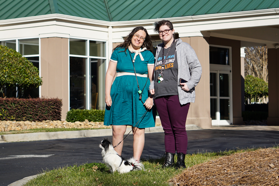 Veronica, a woman with long curly brown hair wearing a dark teal dress with a white belt and collar stands in front of a hotel.  In front of her sits Hestia, a small white and black Japanese Chin dog with a smushed face wearing a purple vest.  Next to them stands Scarlet, who has short hair that is shaved on the sides and is turquoise.  They are wearing purple pants and a grey top and sweater.