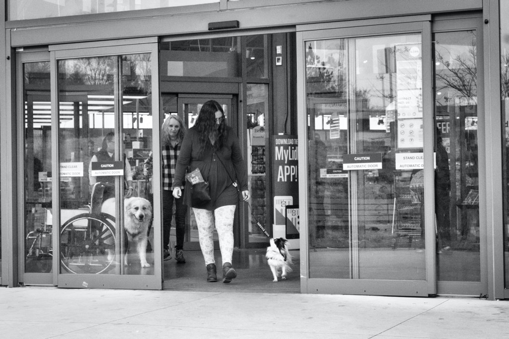 A black and white photo of Veronica with Hestia leaving Lidl, looking at each other as they pass through the opening automatic doors.