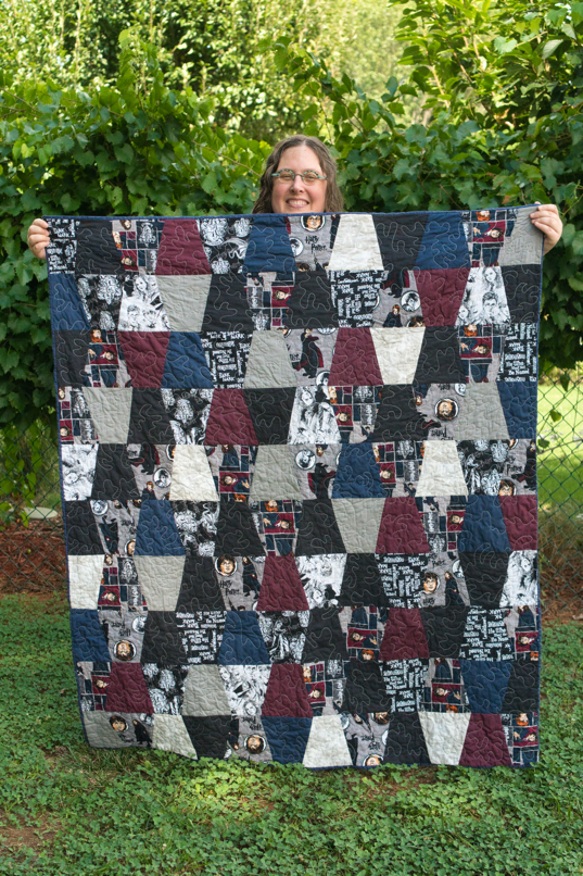 Veronica smiles while holding up the front of the Harry Potter quilt.