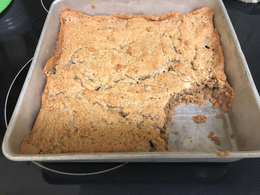 Caramel blondies in the pan with a piece removed.
