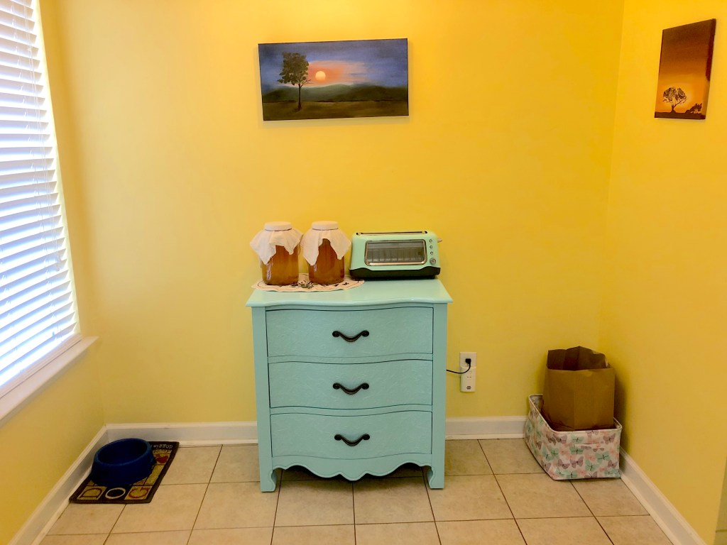 This picture shows our entire dining nook area.  The cabinet sits in the middle of the area against the wall underneath a painting of a sunset in a pink and blue sky done by my mom.  There are two one-gallon jars of kombucha brewing on top of the dresser, and a turquoise toaster.  To the right of the dresser is a brown paper bag for our compost which is in a storage container that has pink, purple, and teal butteries on it.  On the right wall there is an African sunset.  To the left of the dresser is a dog water bowl on a dog themed mat underneath a window.