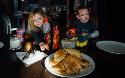 Young girl reaches for pancakes in a high pile.