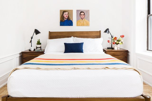 rental bedroom decorated with colorful throw and wall art