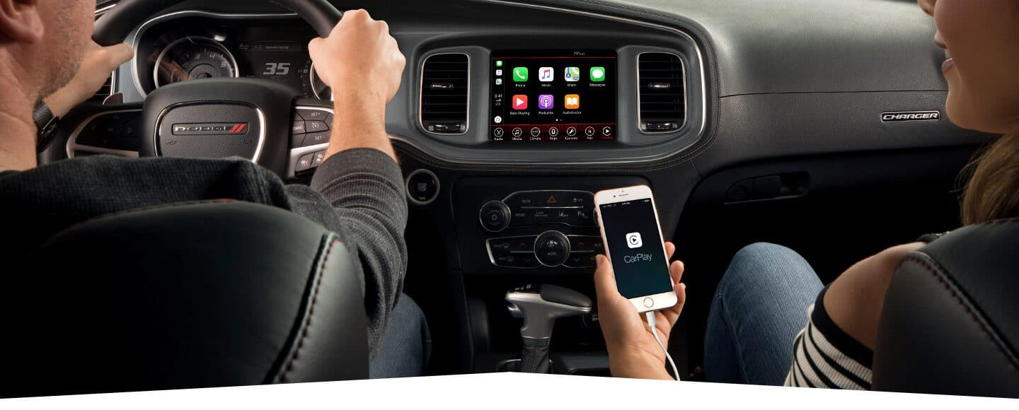 hight resolution of interior view of a man driving a 2019 dodge charger with woman in the passenger seat