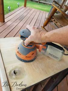 Sanding the wood under veneer that was removed on a Veneer Removal on a Dixie Nightstand / Painted Furniture Makeover