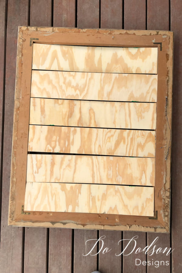 Upcycle picture frames with plywood to create faux shiplap wall decor.