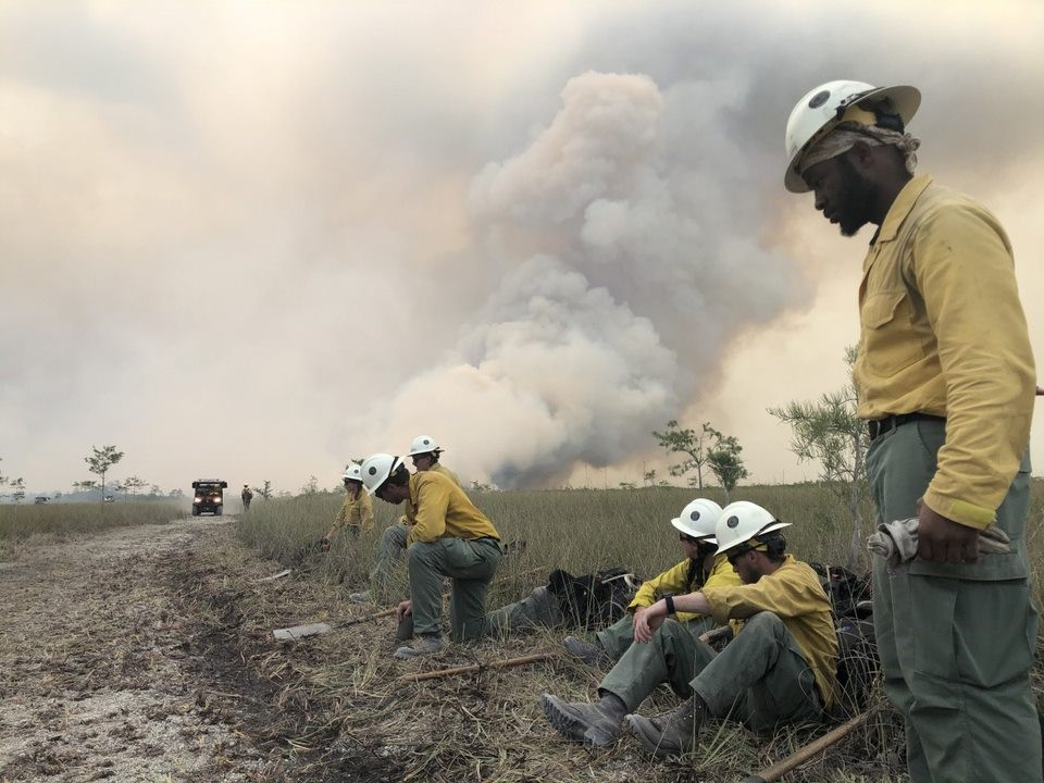 Jackson Hotshots beside a road with smoke billowing in the background.