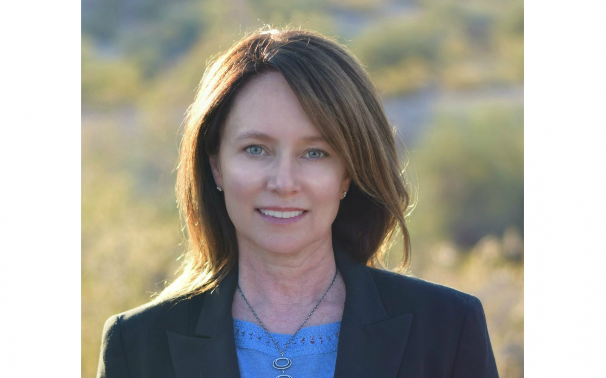 A headshot of a woman, Brenda Burman, standing in front of green trees. She's wearing a blue shirt with a black blazer and smiling wide.