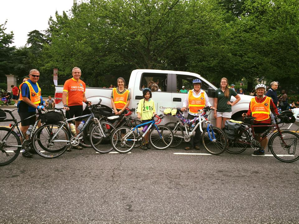 Volunteers of all ages stand with their bikes in front of a park service truck.