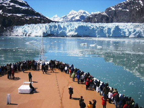 A large group of people stand on the deck of a ship looking across a bay where a glacier runs down from a mountain into the water.