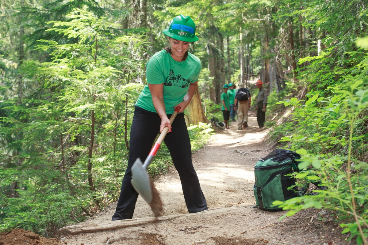 A volunteer uses a shovel to help maintain the trail.