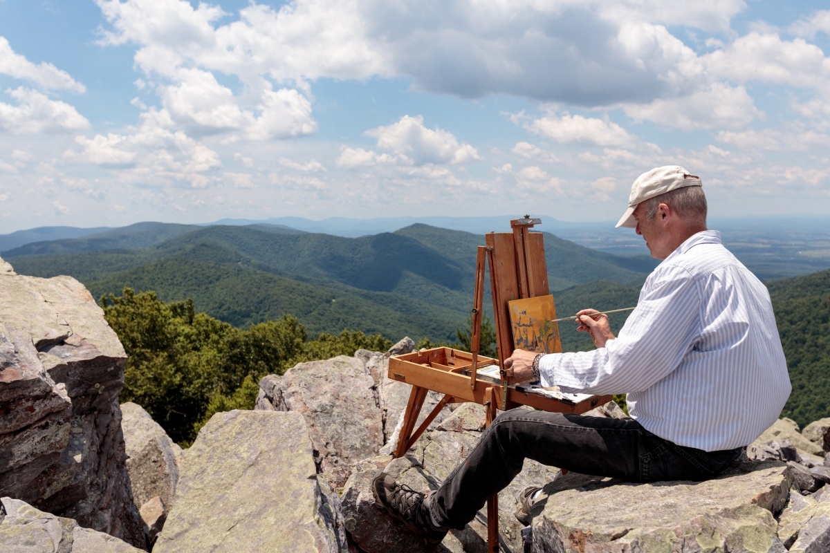 An artist sits on rocks with his easel painting the rolling green hills in front of him.