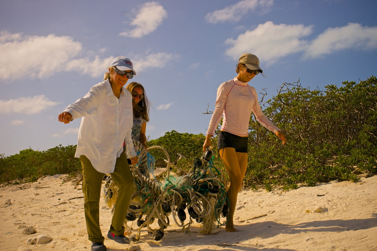 Three volunteers lug a mass of ropes and clams up the beach.