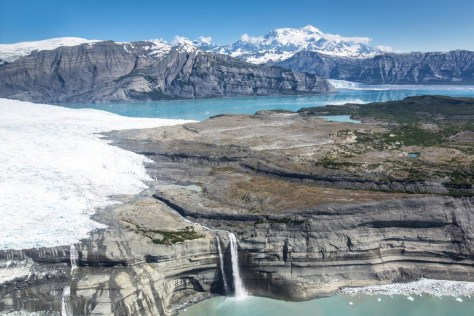 An aerial photo of mountain ranges and massive glaciers cover a wide landscape running down to blue inlets.